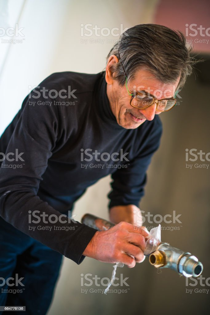 Sealing the pipes. 70-years-old active senior man, construction worker - plumber, working for home renovation stock photo