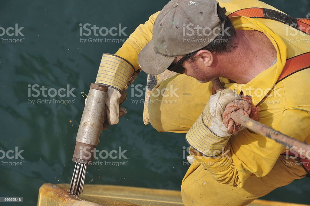 seaman removes rust from ship's hull royalty-free stock photo
