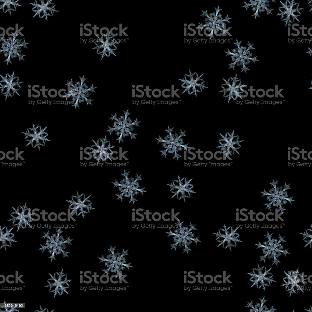 Seamless pattern with cyan snowflakes on black background stock photo