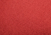 Seamless red colored rough textile fabric background
