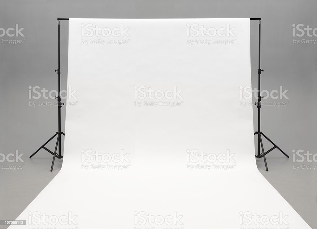 Seamless white background paper hanging on stands-isolated on grey stock photo