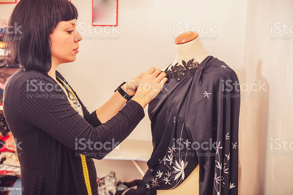 Seamstress Adjusting Cloth on Mannequin stock photo