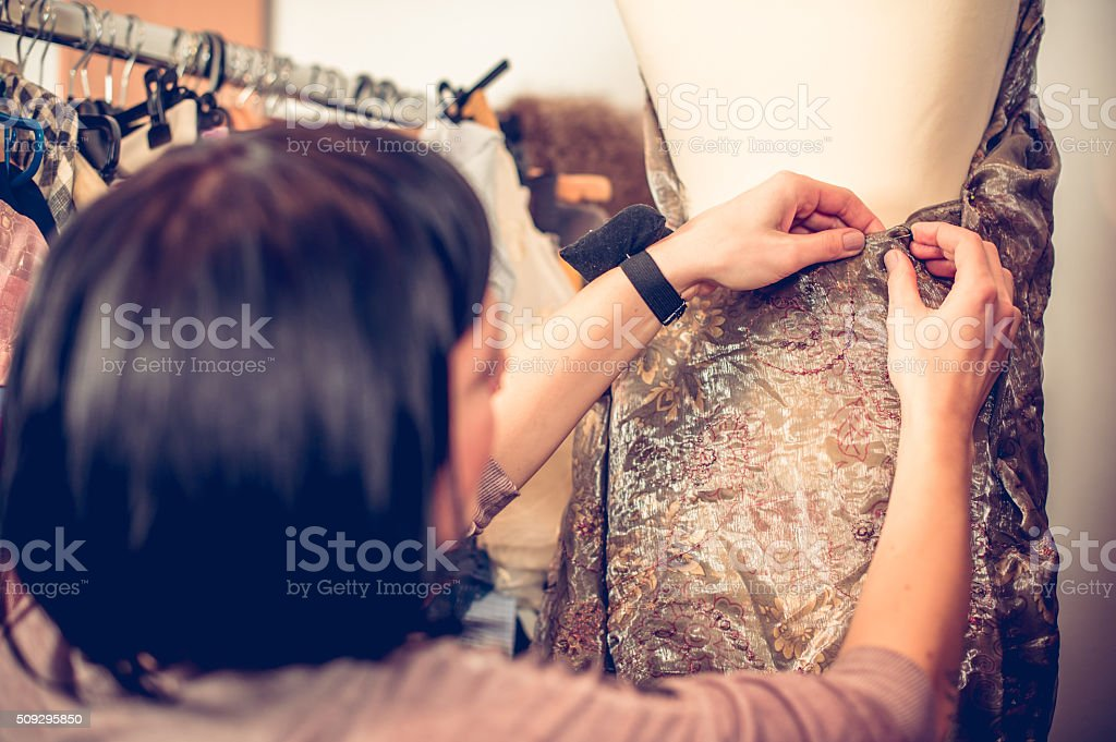Seamstress Adjusting Cloth on Tailor's Dummy stock photo