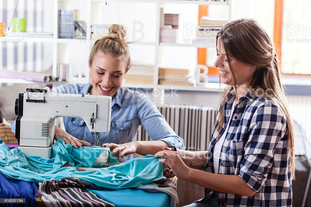 Seamstress and fashion designer sewing together stock photo
