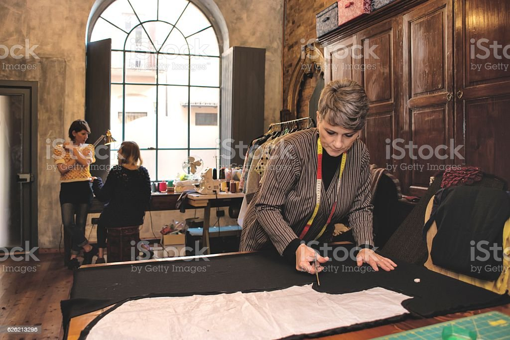 Seamstress and her Teamwork in Working Place stock photo