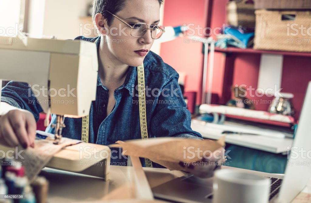 Seamstress Beside a Sewing Machine and Using Laptop stock photo