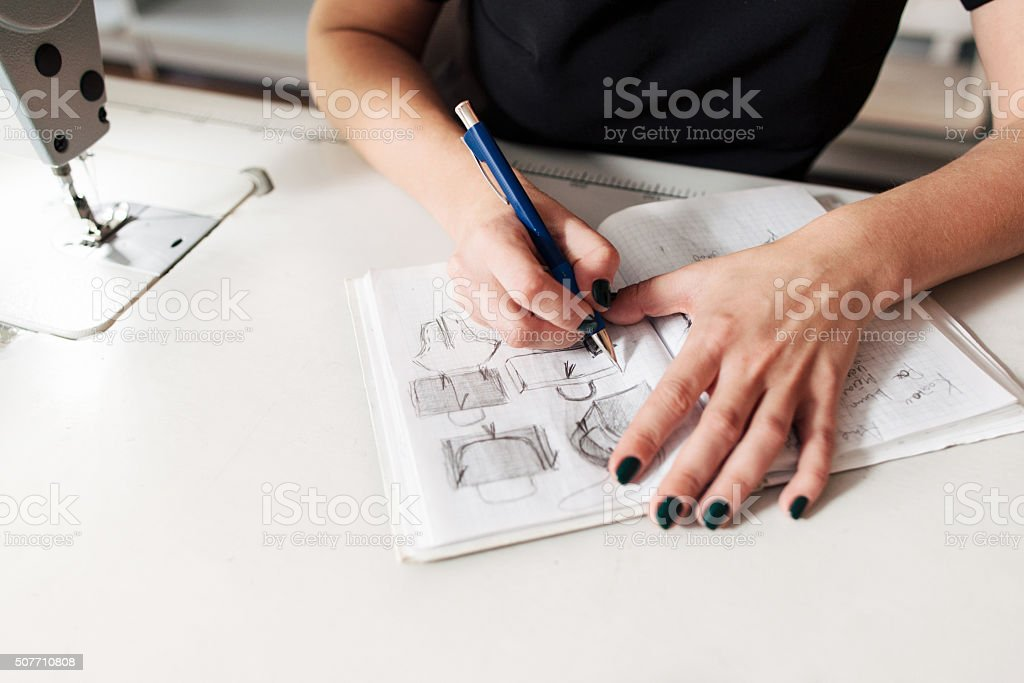 Seamstress creates a sketch of bags stock photo
