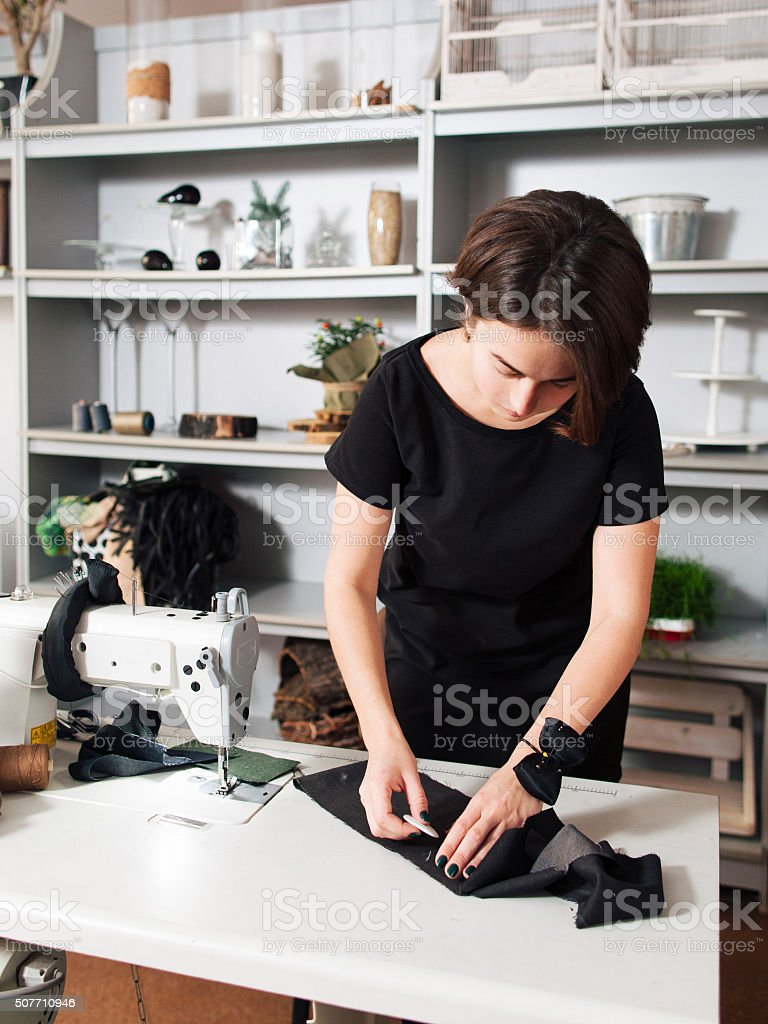 Seamstress creates a sketch on  the fabric stock photo