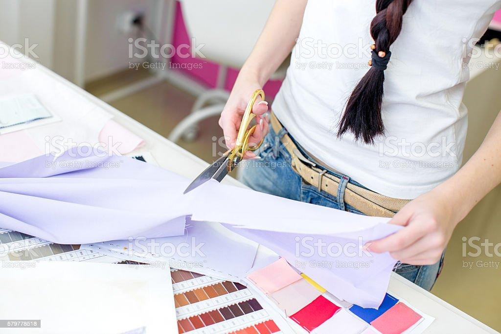 seamstress cuts fabric with scissors stock photo