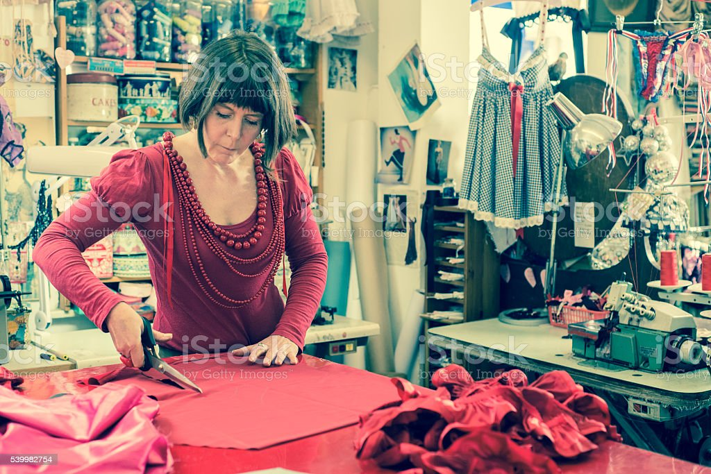 Seamstress Cutting Red Cloth with Scissors stock photo