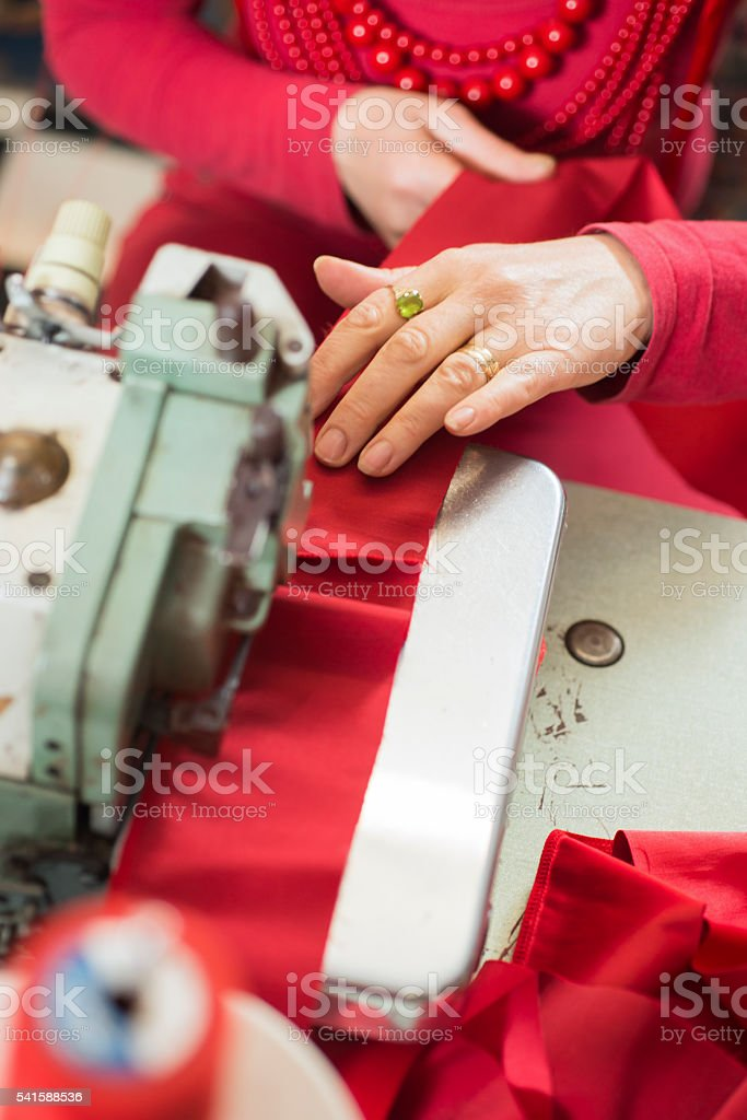 Seamstress' Hand Working on a Sewing Machine stock photo