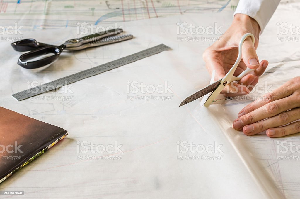 Seamstress is cutting drawing for a dress with scissors stock photo