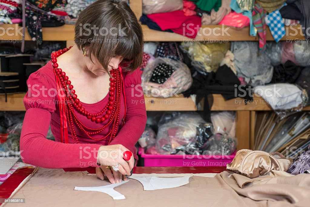 Seamstress Measuring and Cutting Cloth on Cutting Table stock photo