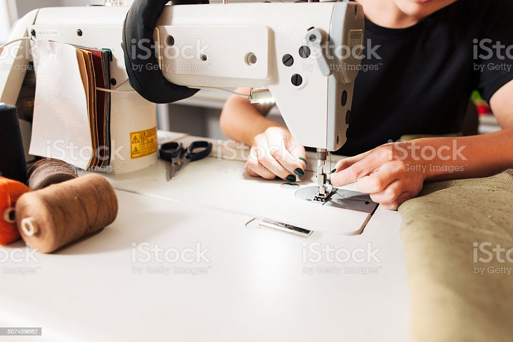 seamstress put thread in needle stock photo