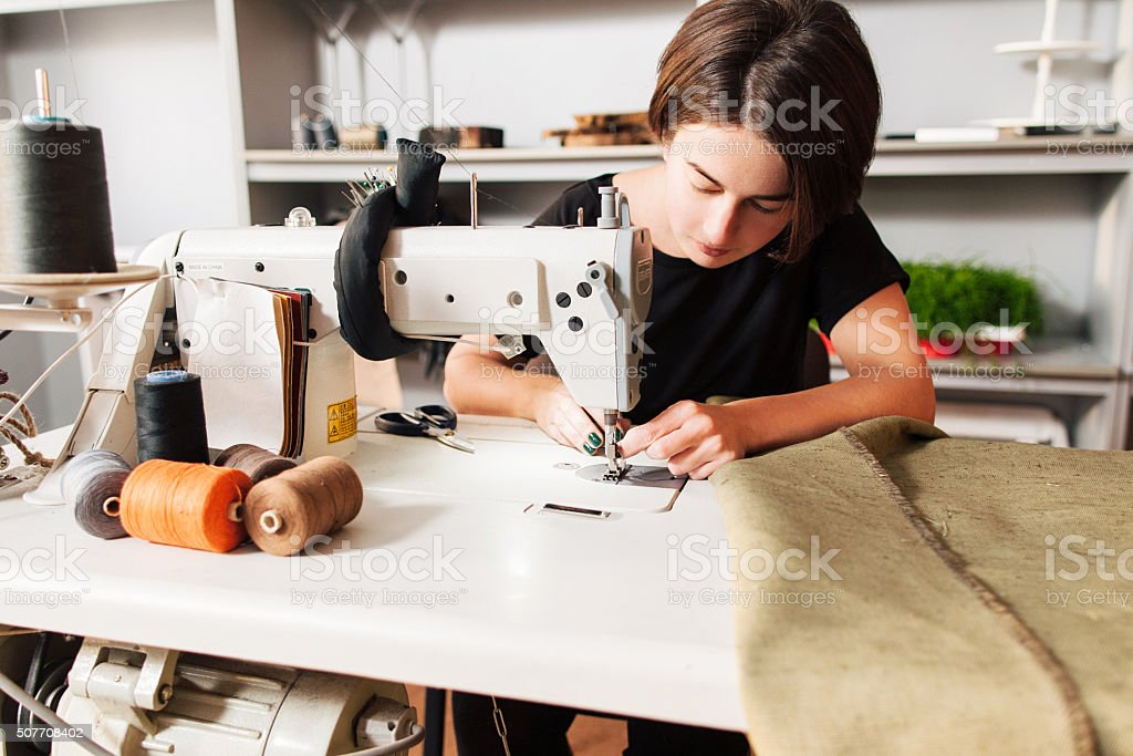 seamstress  put thread in needle. tailor's workplace stock photo