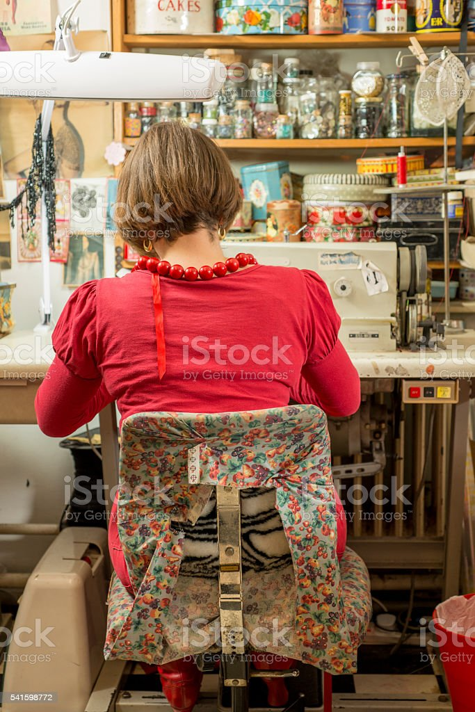 Seamstress Seated and Working on Sewing Machine stock photo
