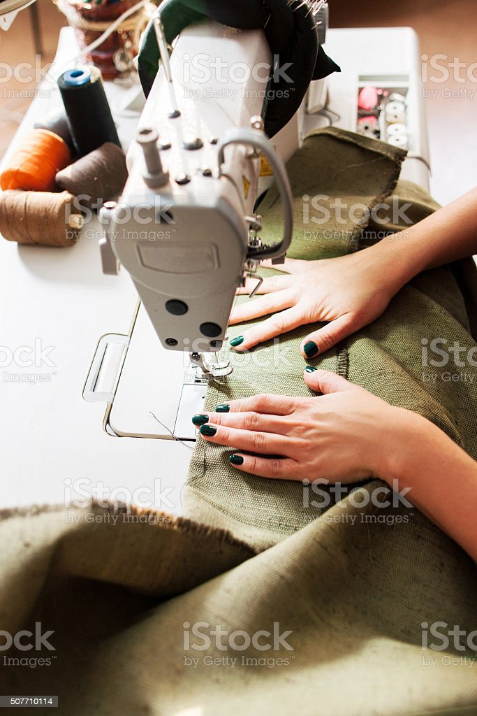 seamstress sews clothes stock photo