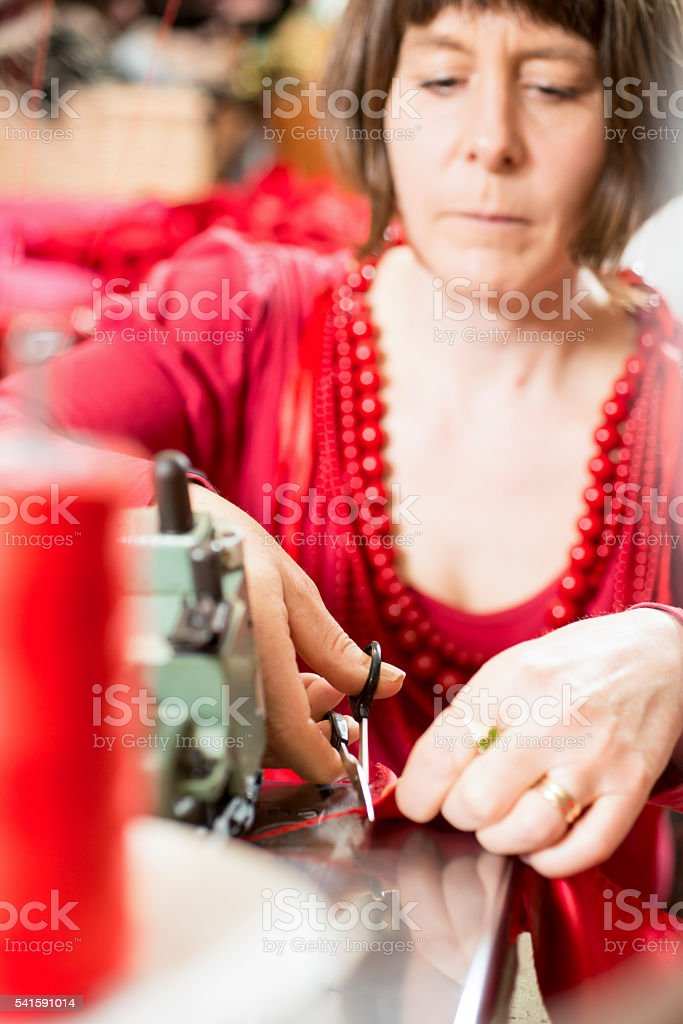 Seamstress Trimming Cloth with Scissors stock photo