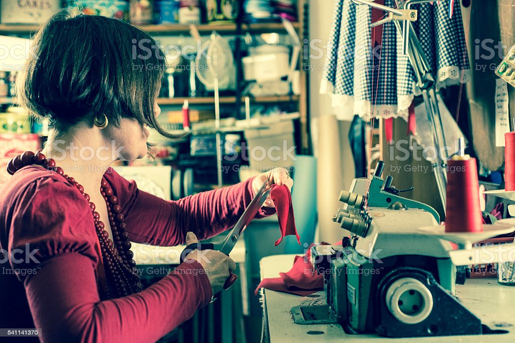 Seamstress Trmming Red Cloth by a Sewing Machine stock photo