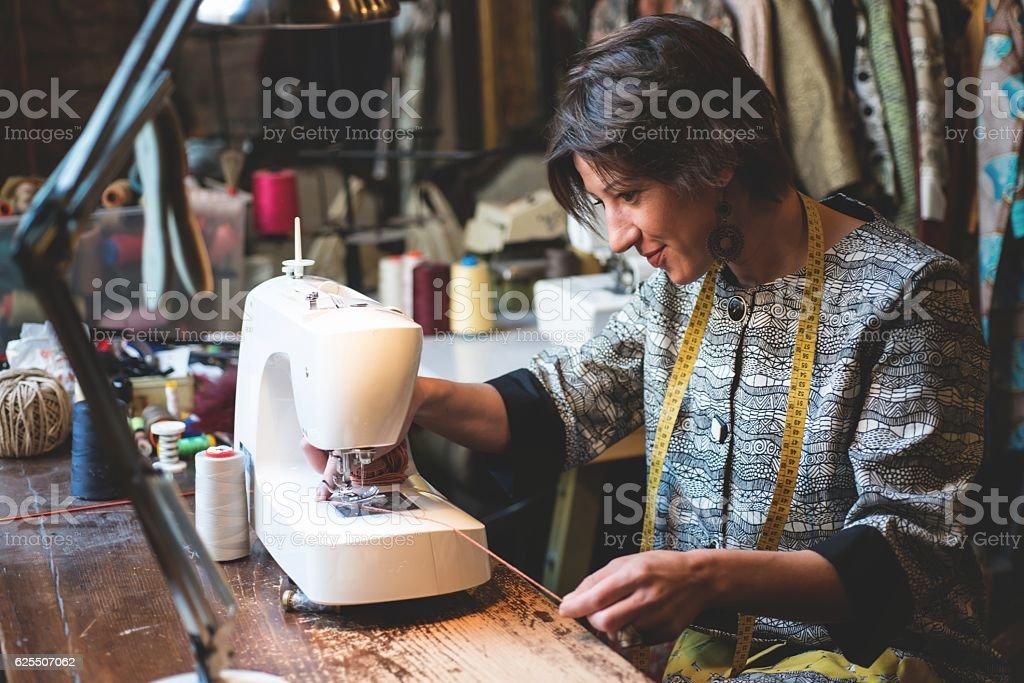 Seamstress Using the Sewing Machine stock photo