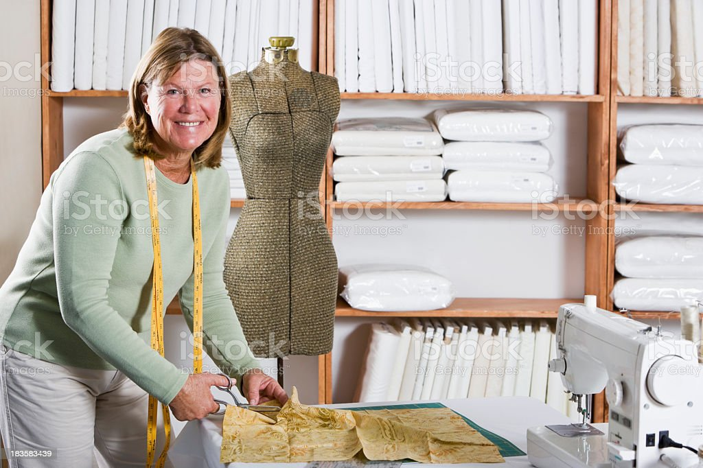 Seamstress working beside dress form stock photo