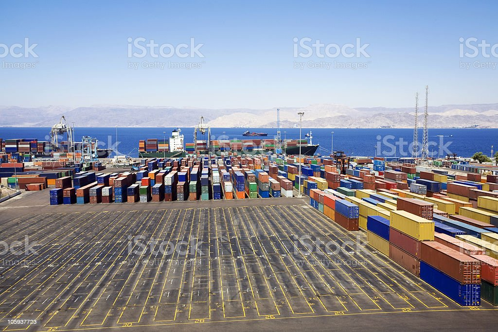 Seaport loading dock with a freighter and stacked containers royalty-free stock photo