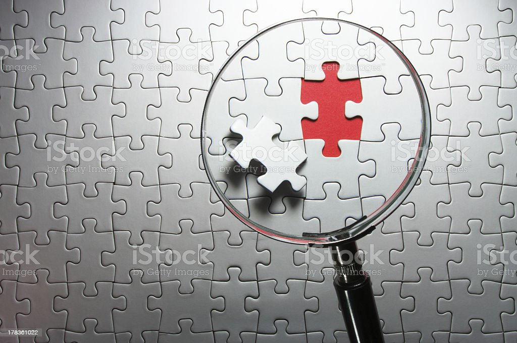 Search for missing puzzle pieces with a magnifying glass stock photo