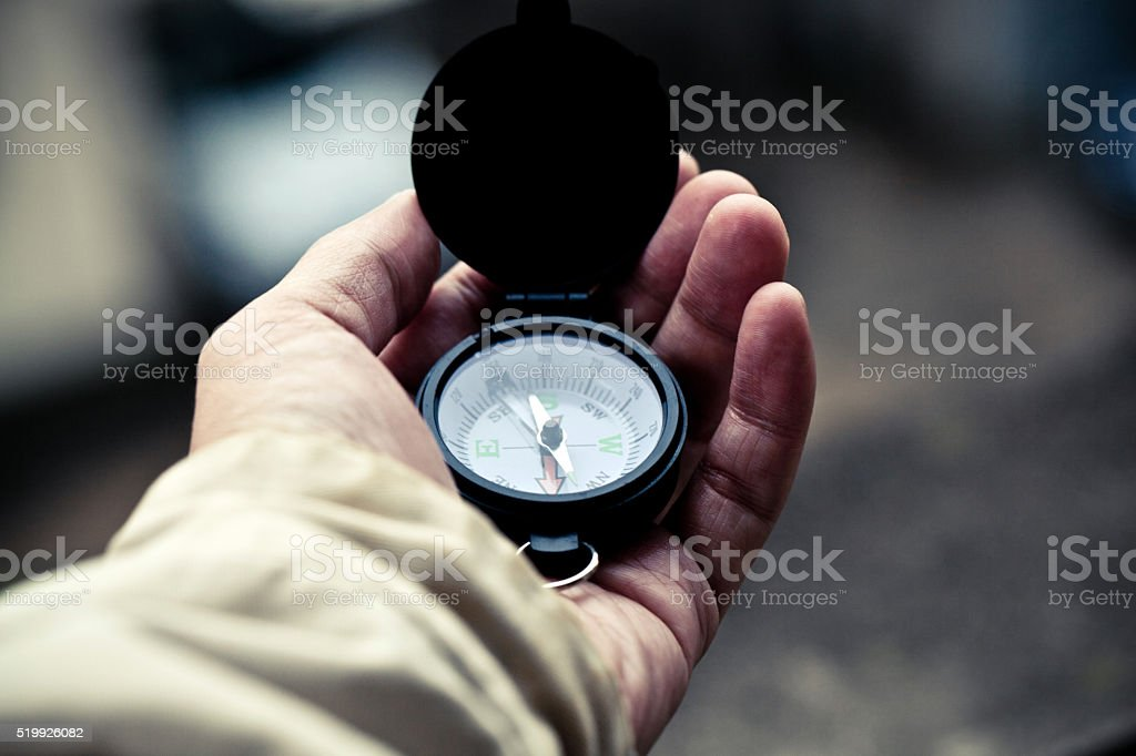 Traveler man searching direction with a compass