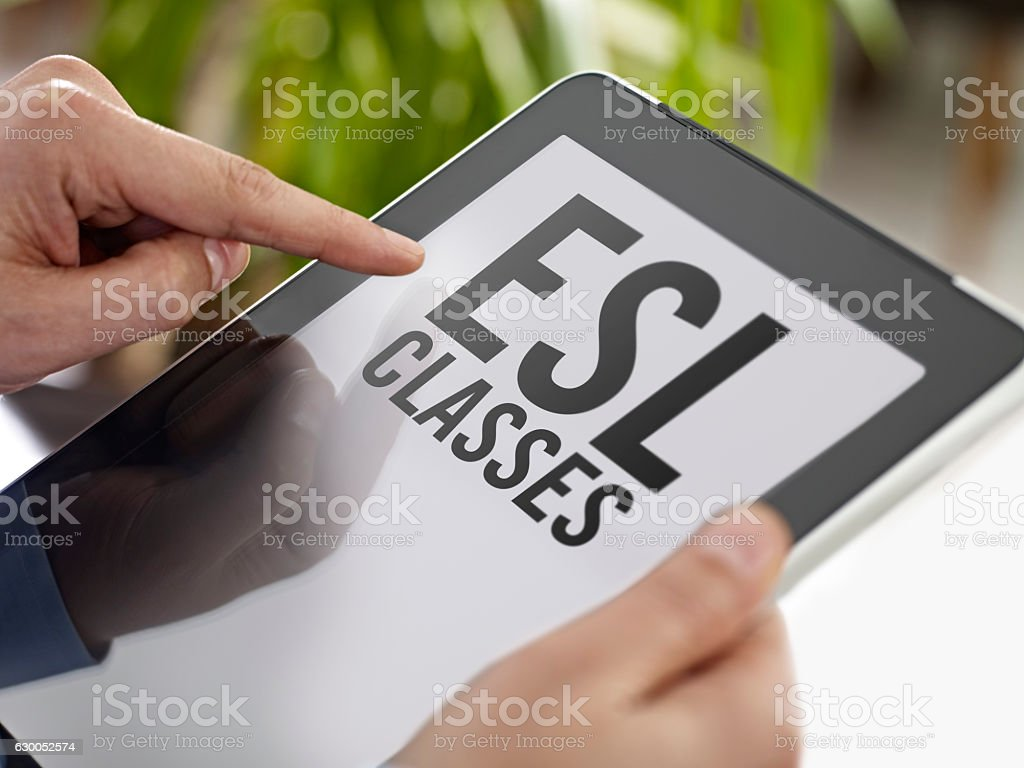 Searching for ESL classes on tablet computer stock photo
