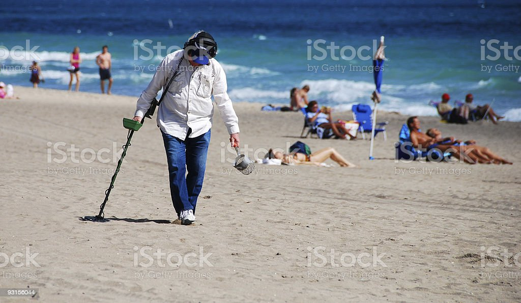 Searching the beach with a metal detector stock photo