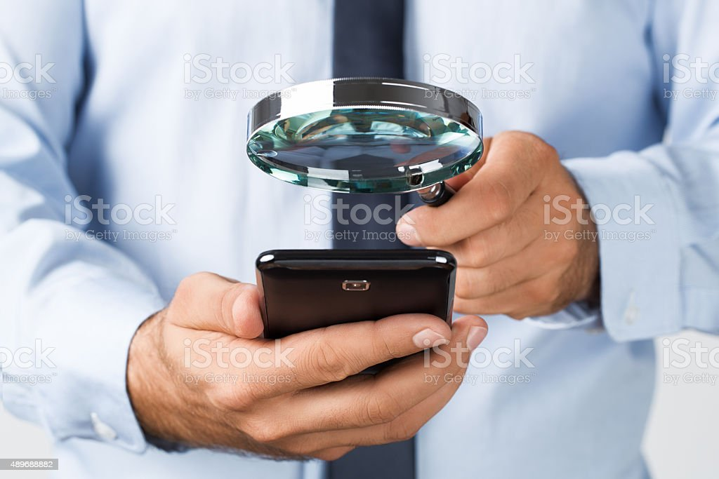 Searching/spying on the mobile phone stock photo