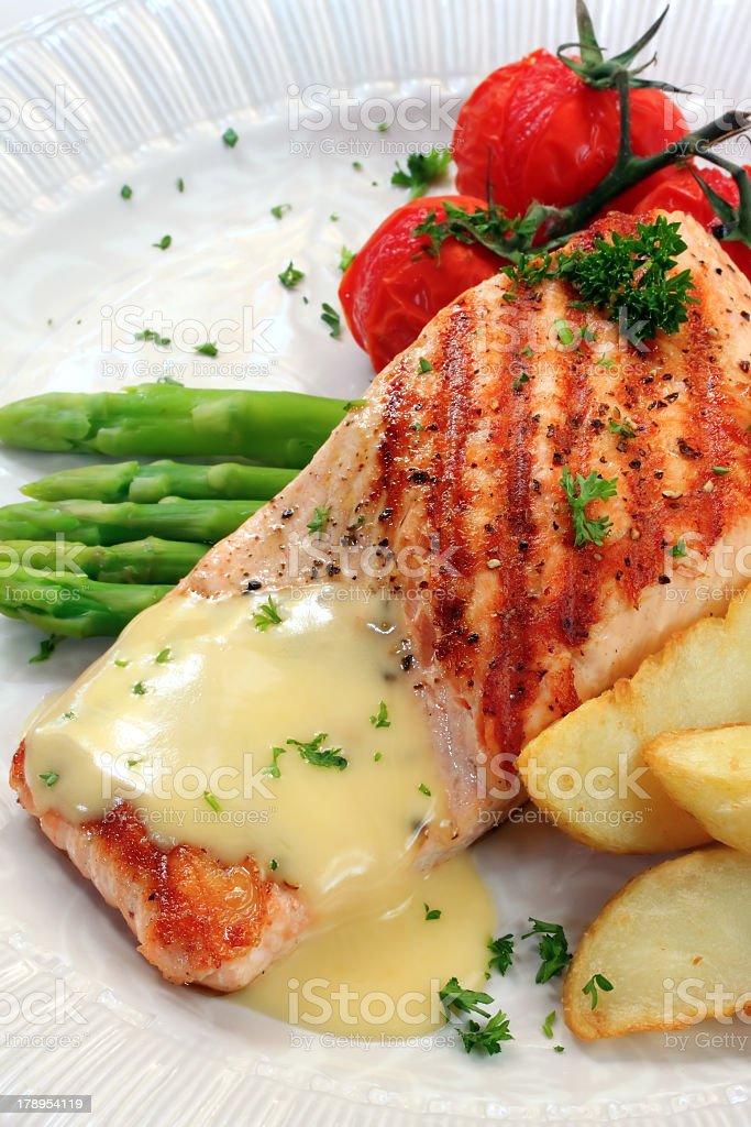 Seared Atlantic salmon with veggies in a hollandaise sauce stock photo