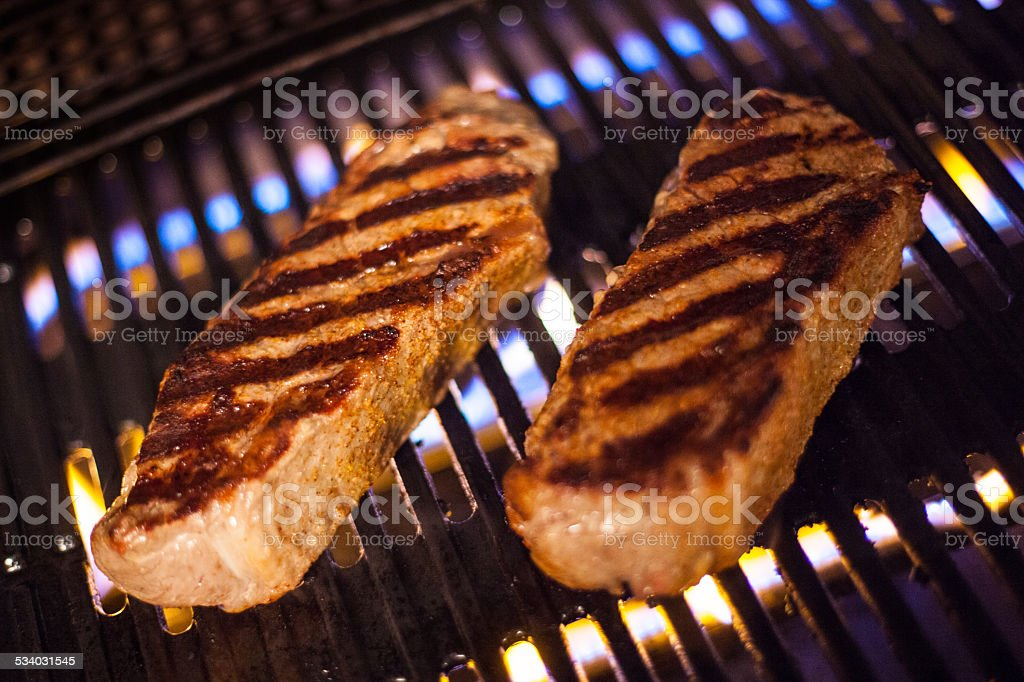 Seared New York Strip Steaks on a Flaming Propane Grill stock photo