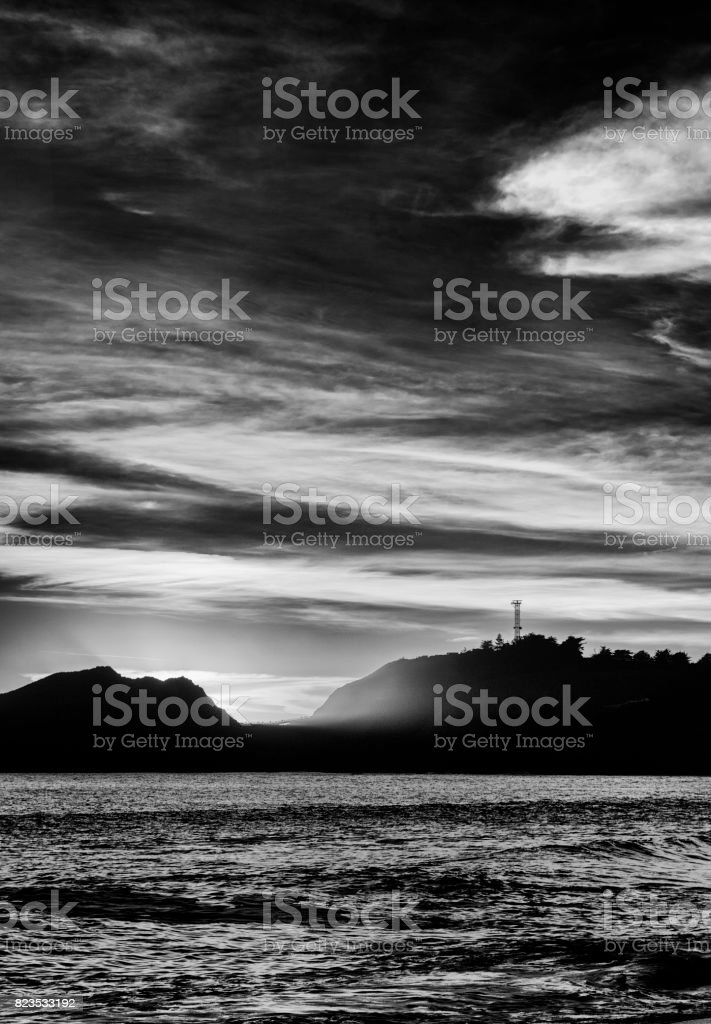 Seascape at sunset with silhouette of a hill on the horizon. Black and white. stock photo
