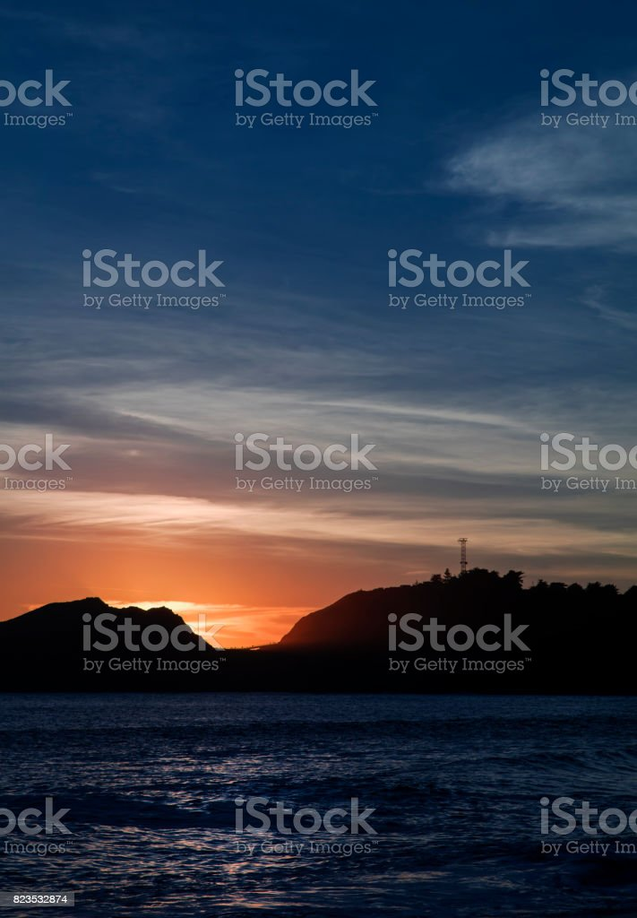 Seascape at sunset with silhouette of a hill on the horizon. Blue and orange Color. stock photo