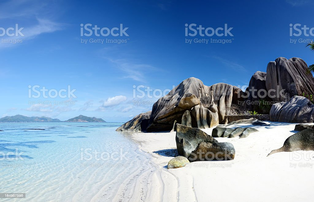 Seascape of Seuchelles white sand beach and large cliffs stock photo