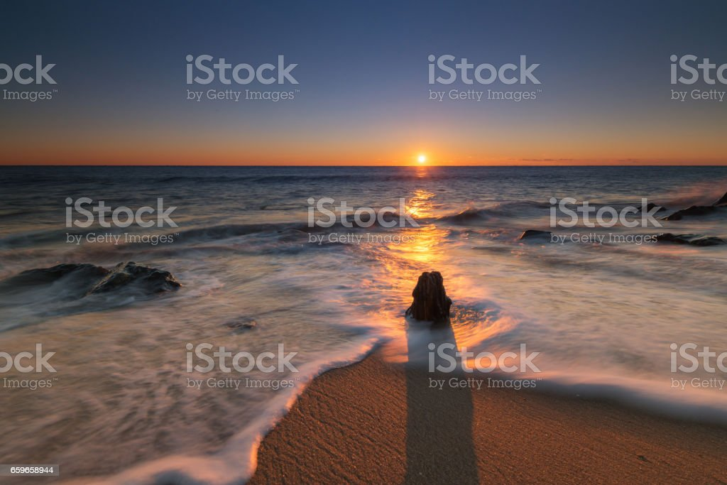 Seascape sunrise with an old piling stock photo
