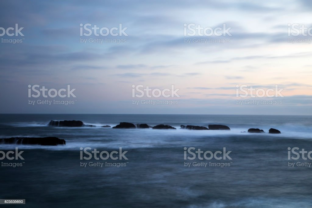 seascape view at sunset with rocks formation out in the Pacific ocean. stock photo