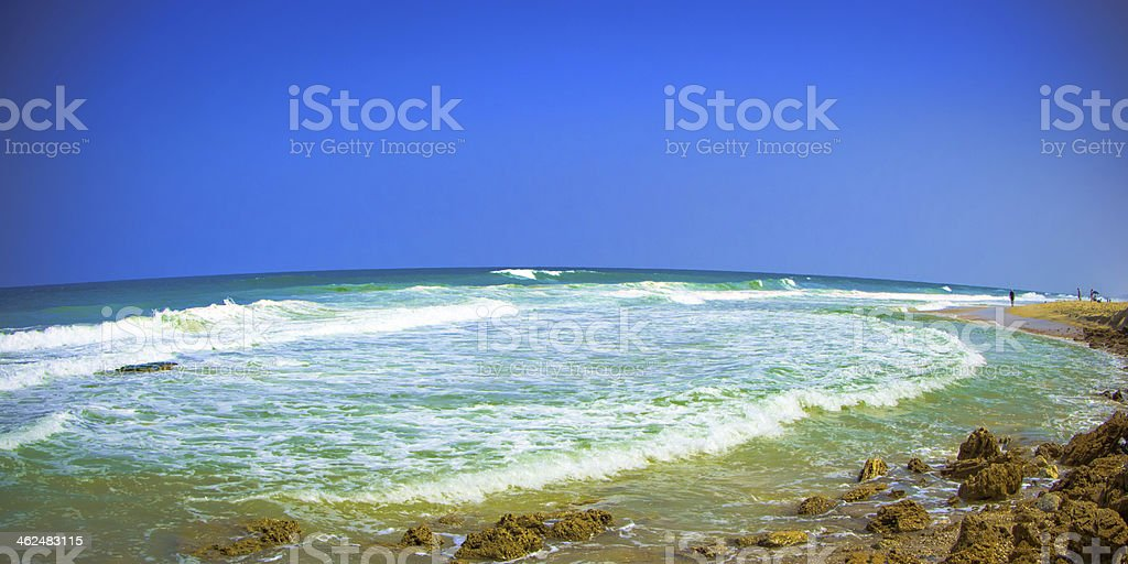 seascape with a cloudless sky, waves and stones stock photo