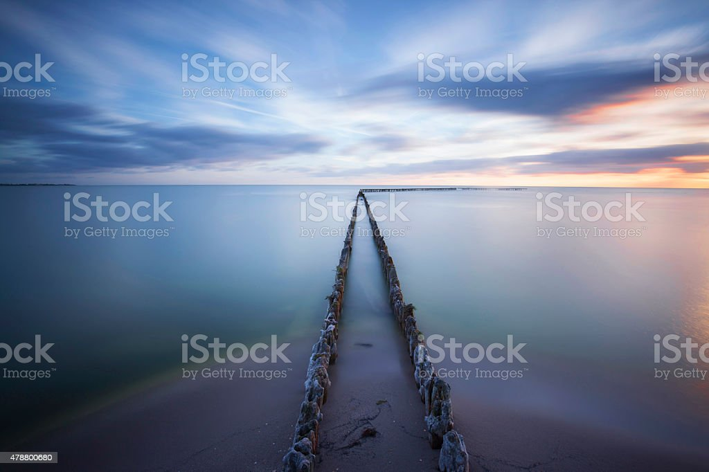 Seascape with breakwaters at sunset stock photo