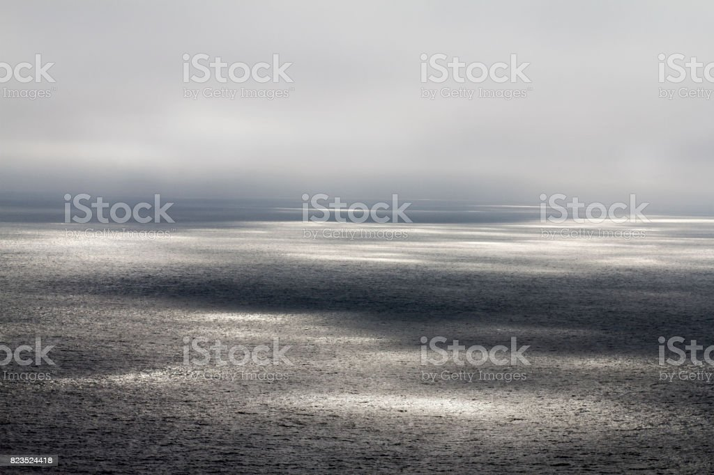 Seascape with ethereal sunbeams on the surface. horizontal stock photo