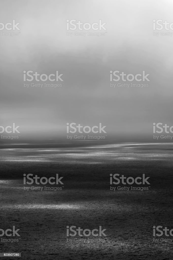 Seascape with ethereal sunbeams on the surface. Vertical composition. stock photo