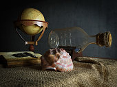 Seashell in interior scene with globe and ship in the bottle