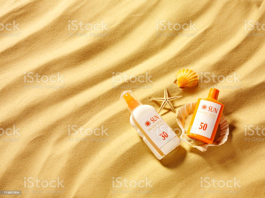 Seashells and Sun Cream Protection in the Sand stock photo