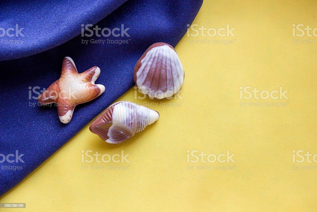 Seashells chocolates on a blue and yellow fabric. stock photo