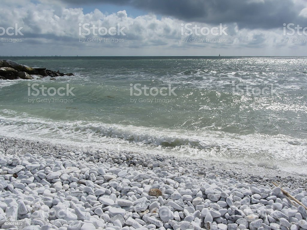 Seashore of pebble beach in a cloudy day at summer stock photo