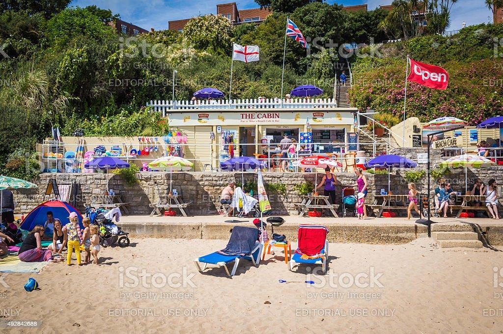 Seaside cafe on crowded beach tourists sunbathers and families England stock photo