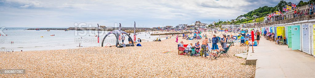 Seaside holiday makers beside colourful beach huts Lyme Regis Dorset stock photo