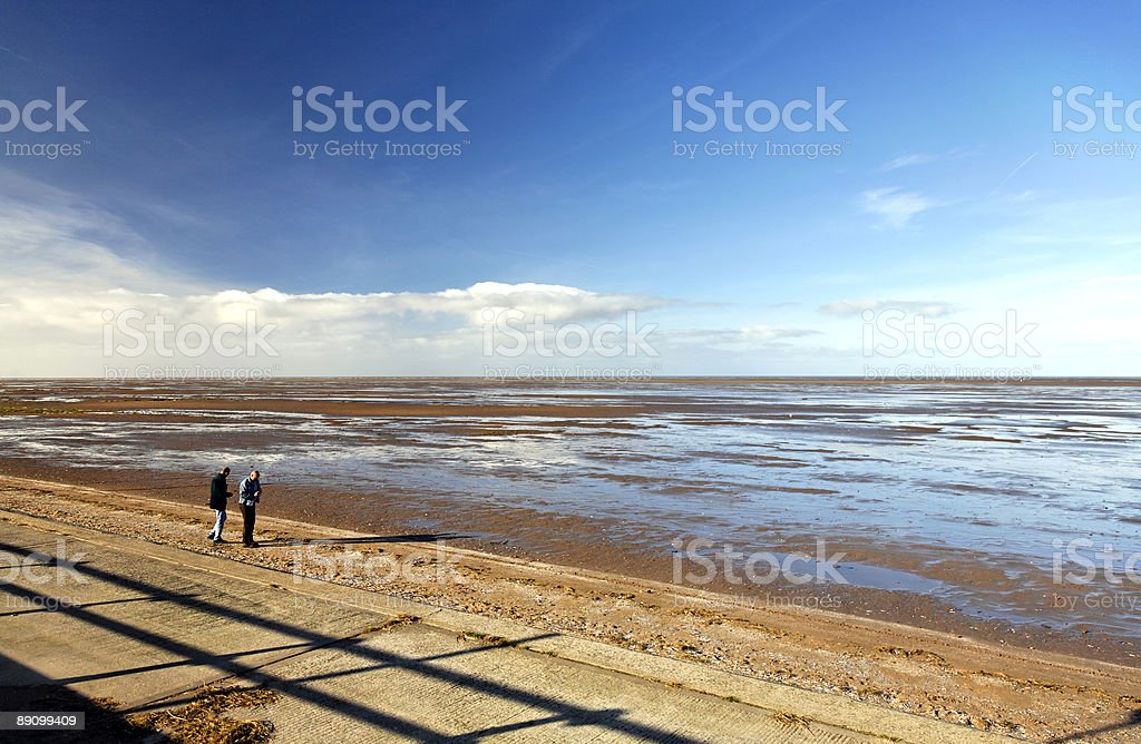 Seaside Mudflat/Beach with Two Men Walking in Middle Distance royalty-free stock photo
