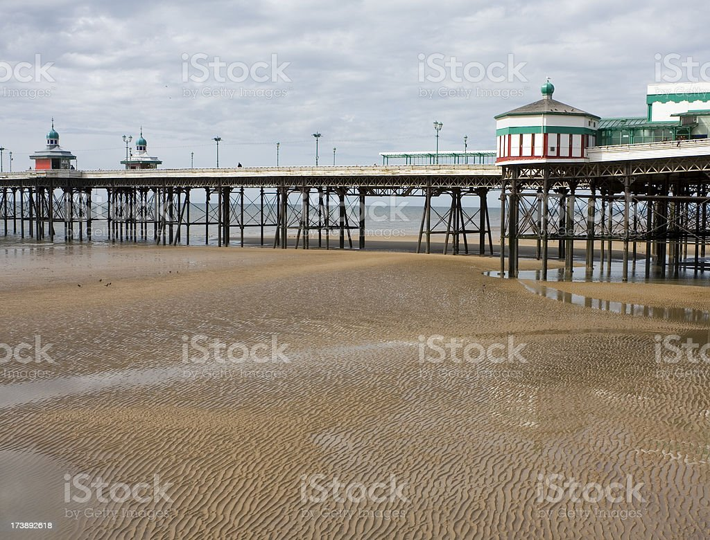 Seaside pier, patterns in the sand stock photo